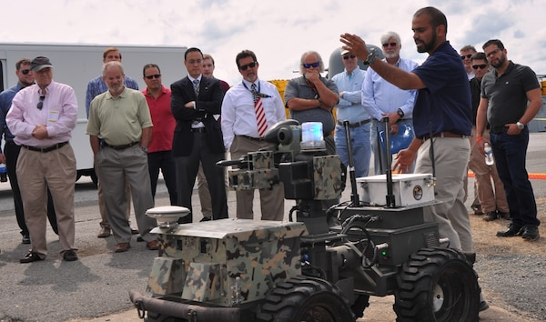 IMAGE:DAHLGREN, Va. (Sept. 12, 2017) - Navy scientist Jamshaid 'JD' Chaudhry briefs visitors on the Weaponized Autonomous System Prototype (WASP) after the Sly Fox Mission 22 demonstration held at Naval Surface Warfare Center Dahlgren Division. The demonstration featured the capabilities of the Collaborative Aerial Network for the Autonomous Remote Engagement System (CANARES) rapid prototyping technology developed by Mission 22 junior scientists and engineers. CANARES consists of an unmanned aerial vehicle, unmanned ground vehicle, and a command and control station.