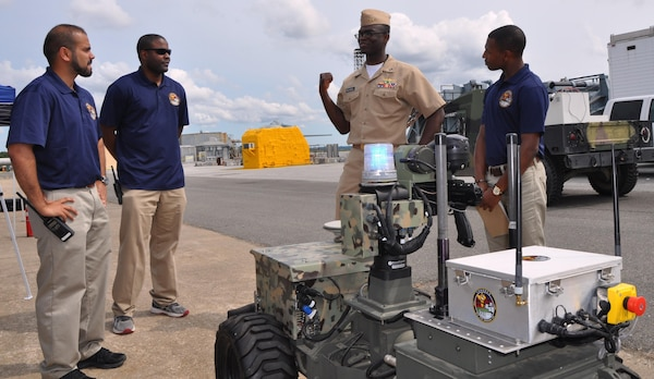"IMAGE: DAHLGREN, Va. (Sept. 12, 2017) - Navy Sly Fox Mission 22 junior scientists and engineers brief Lt. Akwasi Fosu on the new capabilities of Weaponized Autonomous System Prototype (WASP) after a demonstration held at Naval Surface Warfare Center Dahlgren Division.  The seven-member Mission 22 team integrated WASP with an unmanned aerial vehicle (UAV) to provide an aerial perspective for increased situational awareness. Navy civilian and military personnel witnessed the Mission 22 demonstration of the Collaborative Aerial Network for the Autonomous Remote Engagement System – fully-integrated with the UAV, WASP, and a command and control station while detecting, tracking, and engaging targets on the Potomac River Test Range. Standing left to right are Jamshaid ""JD"" Chaudhry, Allen Woods, Fosu, and Chris Toney."