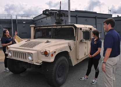 IMAGE: DAHLGREN, Va. (Sept. 12, 2017) - Salima Fenaoui, Michelle Craft, and Joe Gills, left to right, discuss the Autonomous Remote Engagement System installed on the Humvee and the capabilities it provides to the warfighter. They were among the junior scientists and engineers of Navy Sly Fox Mission 22 who developed and demonstrated the Collaborative Aerial Network for the Autonomous Remote Engagement System rapid prototyping technology for several hundred Navy civilian and military personnel who watched it detect, track, and engage targets on the Potomac River Test Range.
