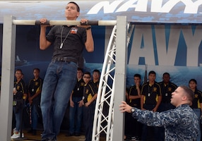 "Petty Officer 1st Class John Torres monitors Jonathon Buerger, a senior attending Media Valley High School during the pull-up challenge sponsored by America's Navy at the 2017 Joint Base San Antonio Air Show and Open House aboard JBSA-Lackland Kelly Field Annex.  Buerger, who completed 25 pull-ups, was amongst 3,200 high school students attending the pre-day rehearsals of the air show and visiting the Navy's virtual reality experience, the ""Nimitz"".  Torres, a Navy recruiter assigned to Navy Recruiting Station Mercado, Navy Recruiting District San Antonio, is a 2000 graduate of Killeen High School."