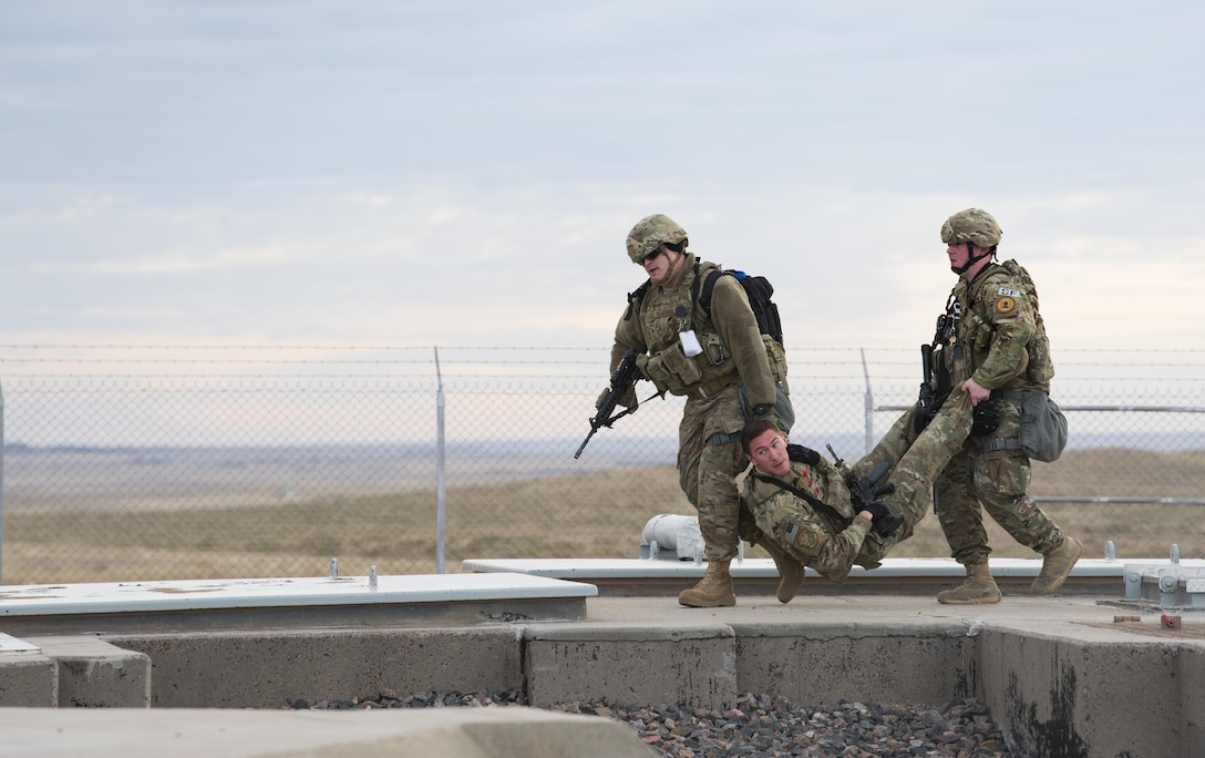 Two airman carry an airman across the ground