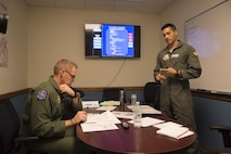 Maj. Jay, 6th Attack Squadron instructor pilot, receives a briefing from a student sensor operator prior to the first solo flight for the aircrew at Holloman Air Force Base, N.M., Nov. 7, 2017. Solo flights build confidence, airmanship and a crew mentality more than academic classroom discussion, or under direct instructor supervision in the cockpit. (U.S. Air Force photo by Tech. Sgt. Amanda Junk)