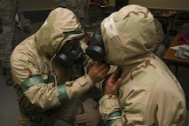 Senior Airman Alex Lopez checks Staff Sgt. Victor Garcia's gas mask and hood during an exercise Nov. 4 at Beale Air Force Base. Squadron. Both Airmen, assigned to the 940th Force Support Squadron, practiced readiness skills in the Ability to Survive and Operate exercise. (U.S. Air Force photo by Senior Airman Tara R. Abrahams)