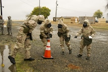 A post-attack reconnaissance team investigates simulated chemical agent detector paper during an exercise Nov. 4 at Beale Air Force Base. The PAR team looked for hazardous agents in the air, as well as unexploded ordnance on the ground. (U.S. Air Force photo by Senior Airman Tara R. Abrahams)