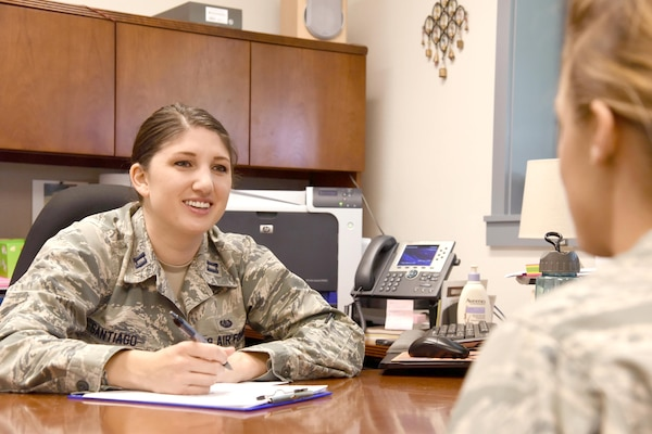 Two service members sit at a desk and speak to each other.