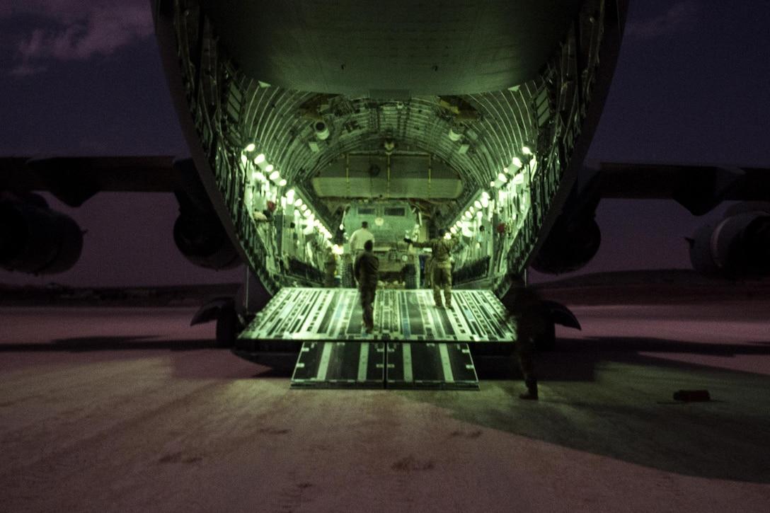 Airmen walk onto the back of an aircraft.