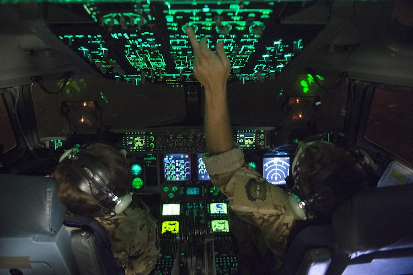 Air Force pilots work the cockpit controls of a military aircraft.