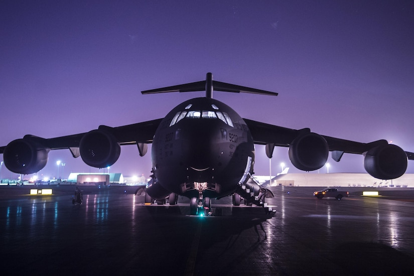 A military aircraft sits on a runway at night with a purple sky in the background.