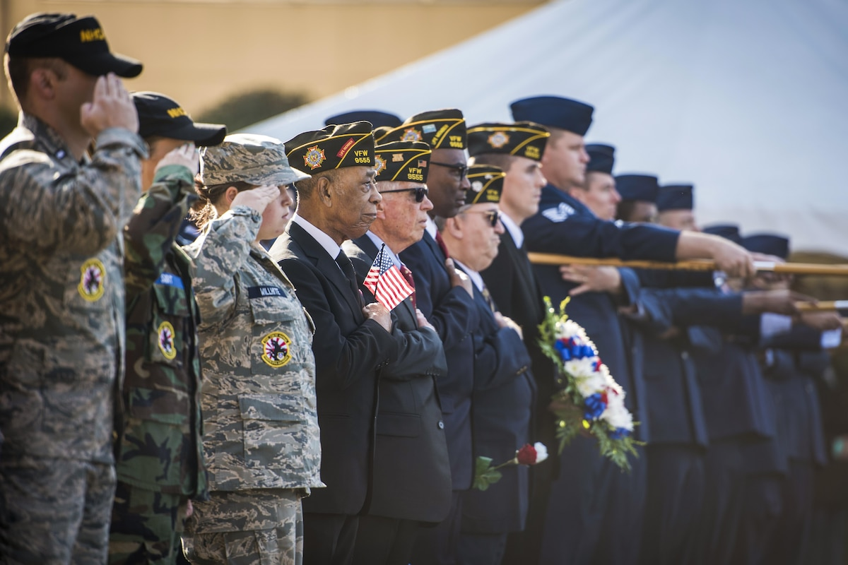 Airmen and veterans salute during a Veterans Day ceremony.