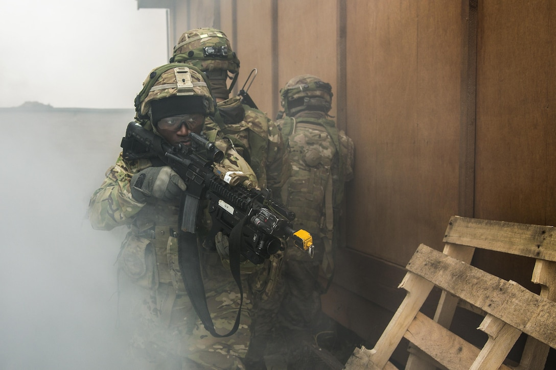 Soldiers with weapons participate in an exercise.