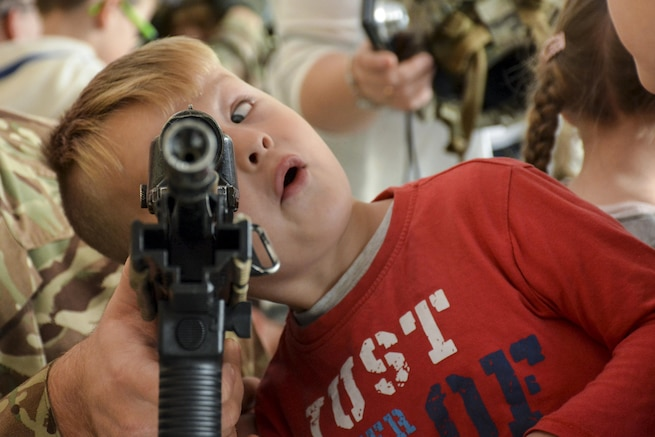A child looked through a military assault rifle.