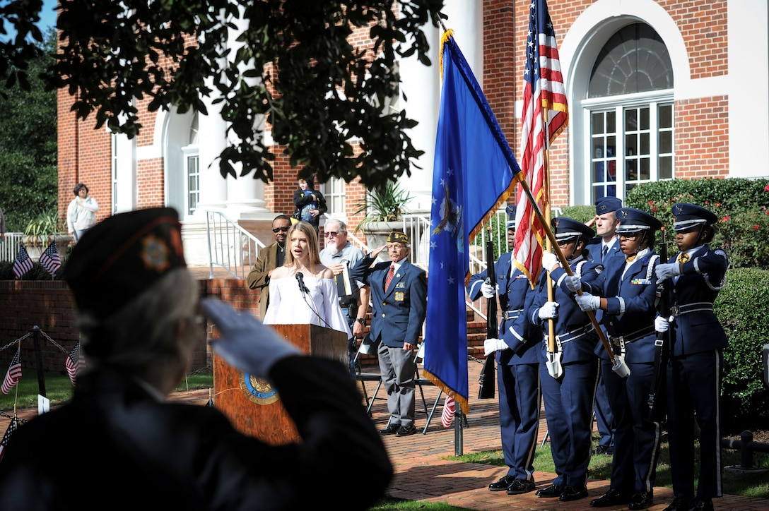 Evans Rhett sings the national anthem as members of West Lowndes High School Air Force Junior ROTC Honor Guard present the colors during a Veterans Day ceremony at the Lowndes County Courthouse Nov. 11, 2017, in Columbus, Mississippi. Members of Columbus AFB and the city of Columbus came together to organize a parade and ceremony to honor veterans. (U.S. Air Force photo by Staff Sgt. Christopher Gross)