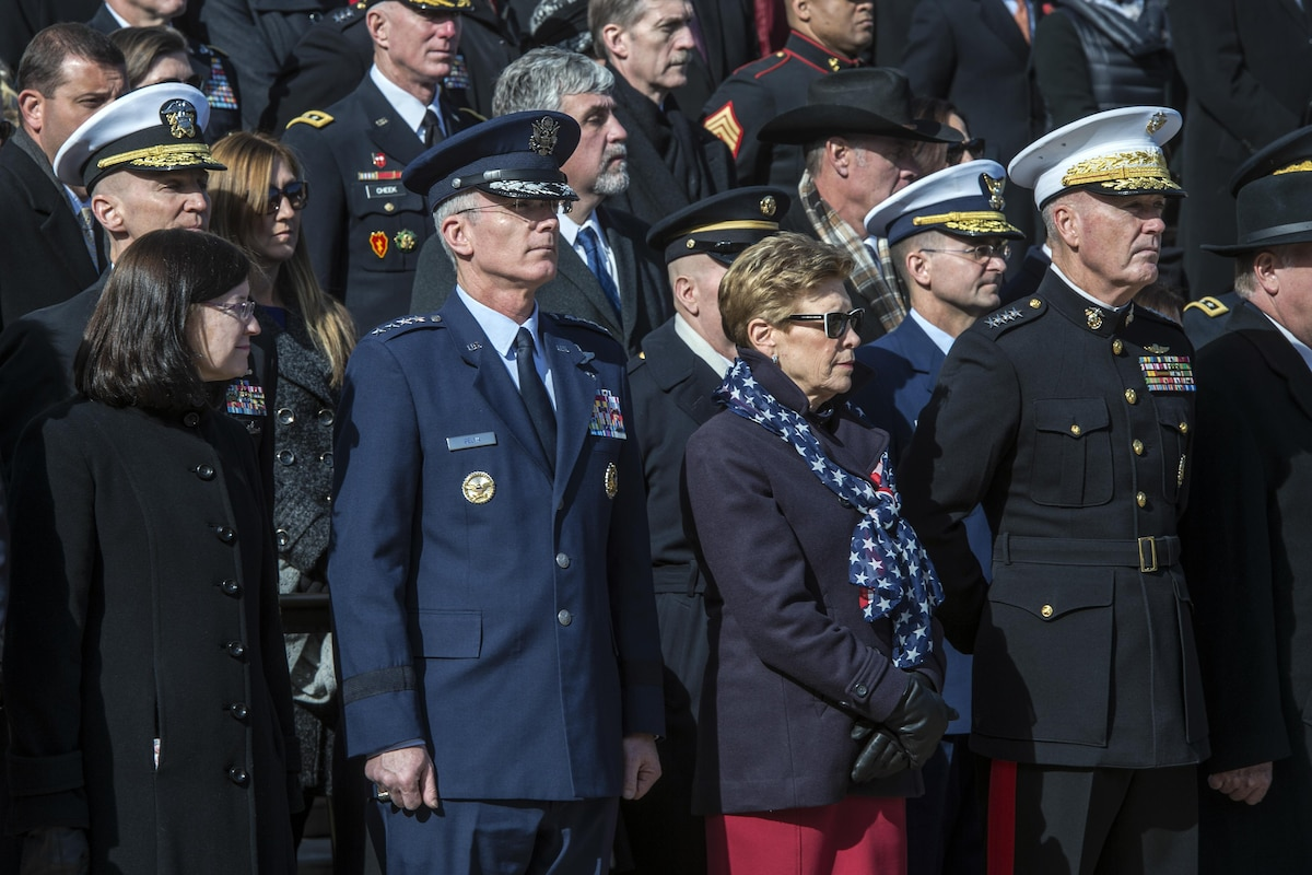 Air Force Gen. Paul Selva and Marine Corps Gen. Joe Dunford and their wives stand during a ceremony.