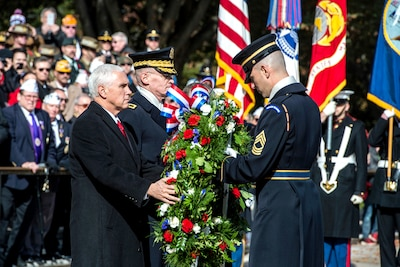 Vice President Mike Pence places a wreath on a stand with the assistance of a service member.