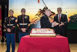 Maj. Alan Thompson hands John Wolfe a piece of cake during the 242nd Marine Corps birthday celebration at DSCC