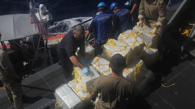 Sailors stack bales of seized cocaine aboard USS Zephyr.