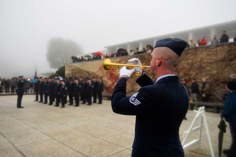 U.S. Air Force Staff Sgt. Ryan Wist, 786th Civil Engineer Squadron water and fuel systems maintenance technician, plays the bugle during a Veterans Day ceremony at Henri-Chapelle American Cemetery and Memorial, Belgium, Nov. 11, 2017. Despite inclement weather, more than 100 veterans and civilians turned up for the ceremony. (U.S. Air Force photo by Airman 1st Class Joshua Magbanua)