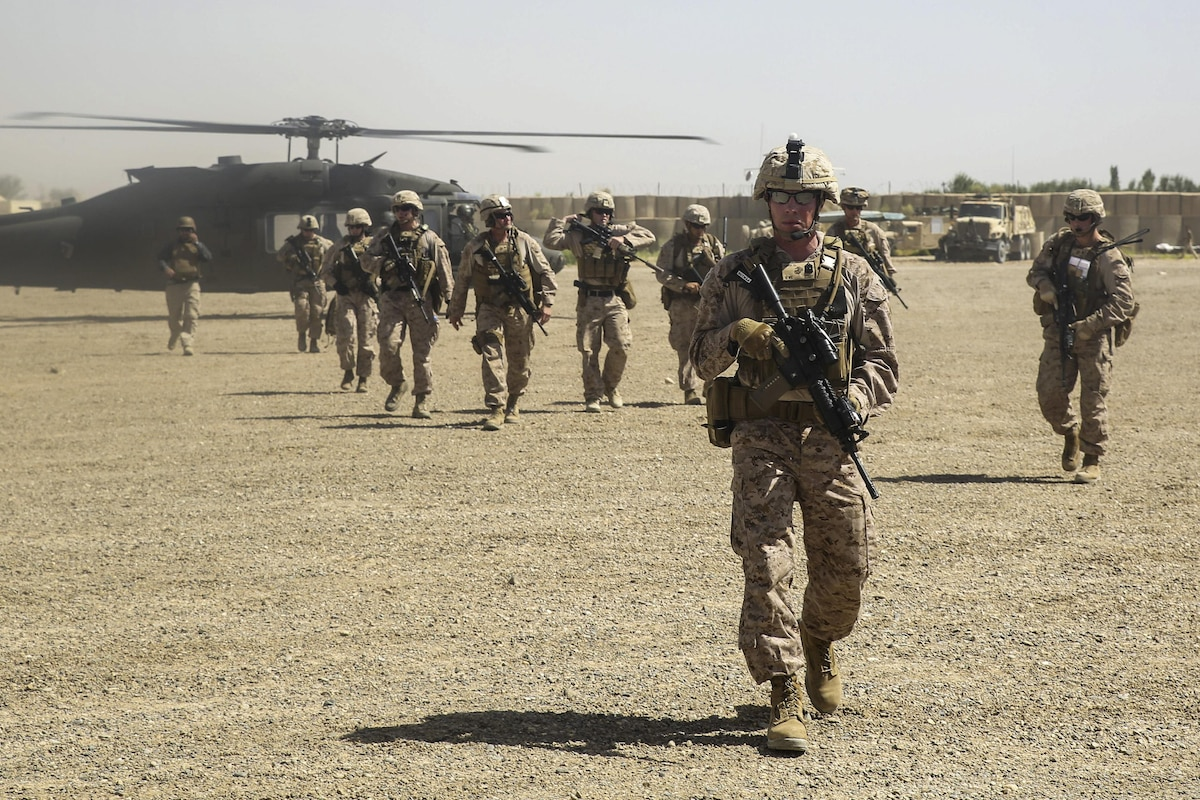 Marines carry weapons as they depart a helicopter