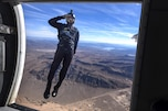 An airman jumps out of an airplane and salutes.