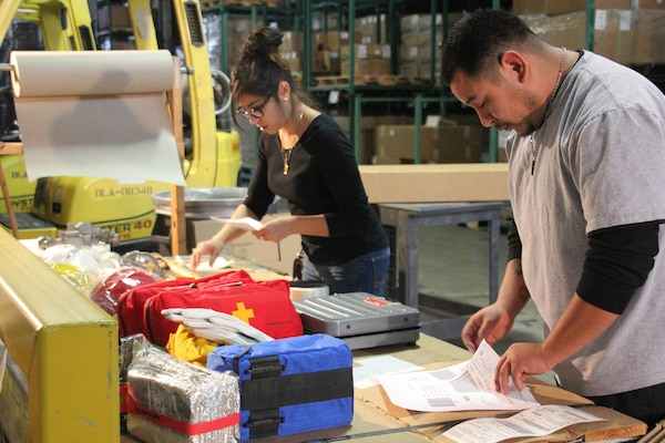 Margarita Rivera-Juarez and Hector Madrigal of the Warehousing Division of DLA Distribution San Joaquin, California, pack firefighting equipment to be shipped to the California Department of Forestry and Fire Protection in support of firefighting efforts.