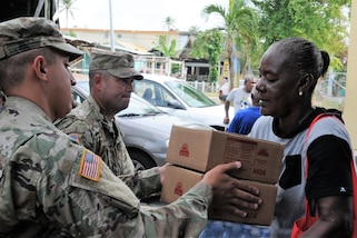 Puerto Rico Army National Guard soldiers provide humanitarian aid as part of the continuous effort to assist residents of affected communities around the island after Hurricane Maria in Piñones, Puerto Rico, Nov. 9, 2017. Food and water were distributed to families in the communities that were flooded as a consequence of the hurricane, leaving the area with extensive losses and lacking basic needs. National Guard photo by Spc. Hamiel Irizarry