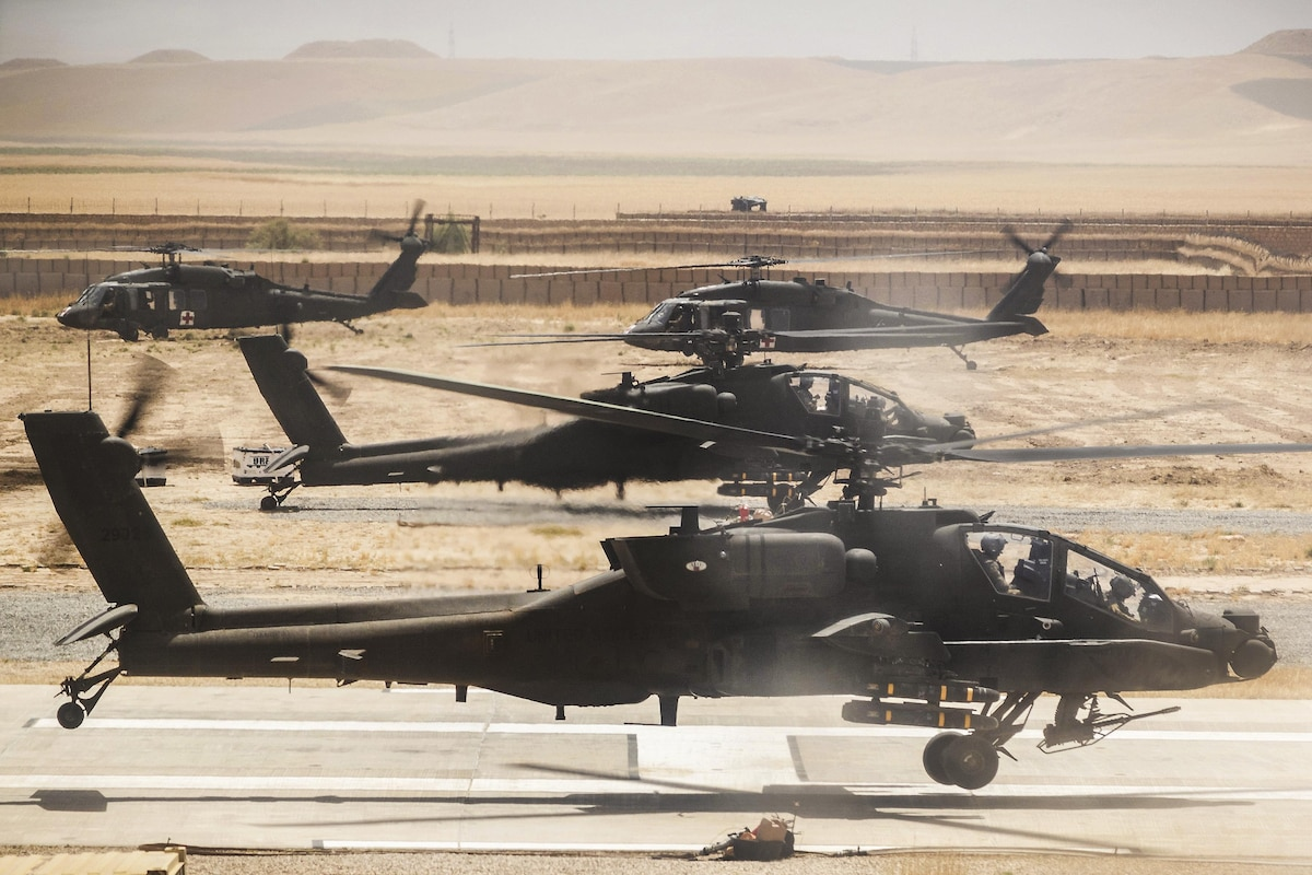 Army helicopters lift off from a runway in Afghanistan