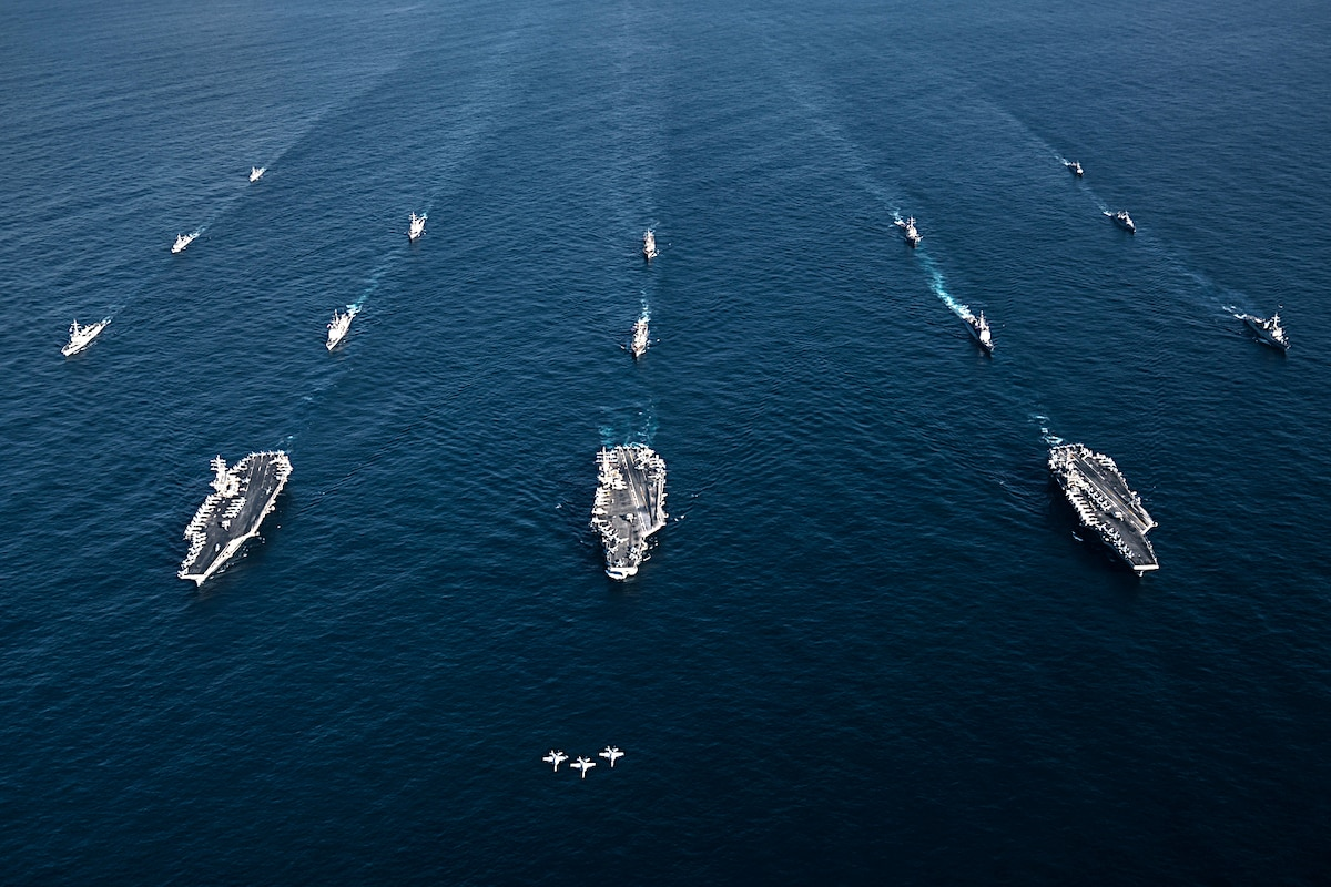 Three jets fly ahead of three carriers in formation in the ocean.