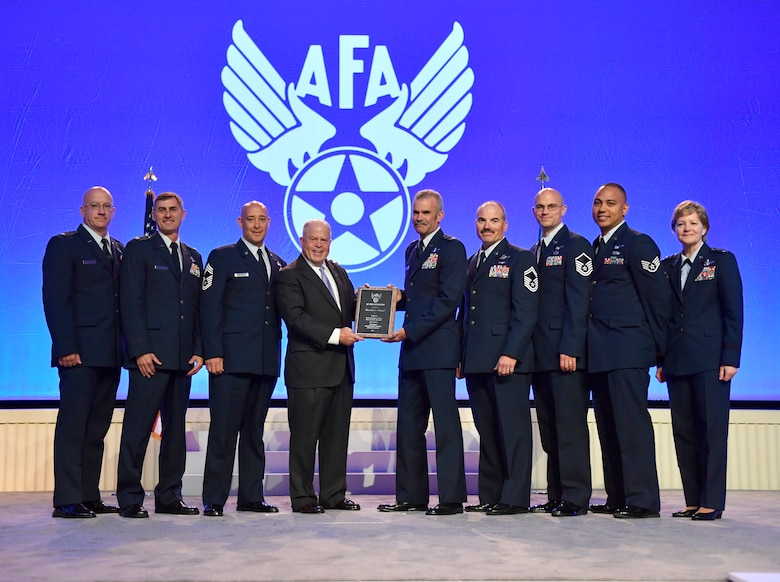 F. Whitten Peters, the Air Force Association chairman of the board, presents the AFA President's Award to the 2016 Outstanding Reserve Aircrew of the year to Lt. Col. Luke Thompson, C-130 Hercules aircraft commander, and the aircrew of GLIDE 68, Sept. 18 at the AFA Air Space Cyber Conference held in National Harbor, Maryland.