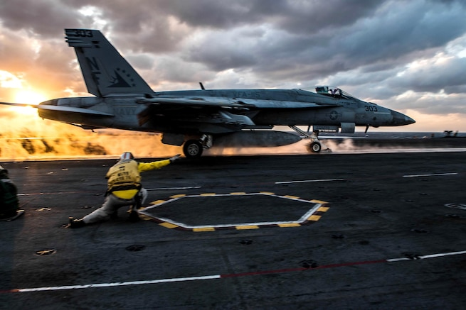 A sailor gives a signal while a jet takes off from an aircraft carrier.