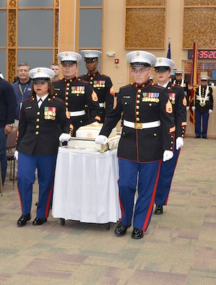 Four Marines roll a cart with a cake into a conference center.