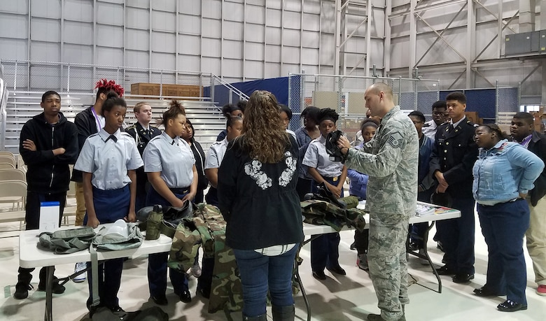 Master Sgt. Brandon Ashcraft, 445th Civil Engineer Squadron wing emergency manager, demonstrates to students from Thurgood Marshall and Meadowdale High Schools how to don a gas mask during the Dayton public schools outreach event the 445th Airlift Wing hosted Oct. 20, 2017.