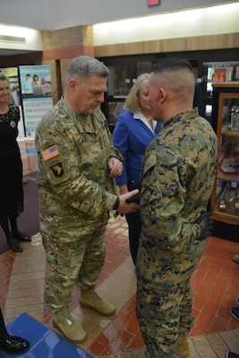 U.S. Army Chief of Staff Gen. Mark A. Milley presents his military coin to Marine Corp. Alexander Cruz while visiting Brooke Army Medical Center in honor of Veterans Day Nov. 11, 2017. Cruz has been undergoing physical therapy with the BAMC Burn Rehabilitation team.