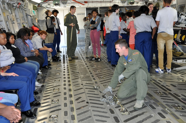 Tech. Sgt. Trevor Dixon, 89th Airlift Squadron loadmaster, demonstrates to a group of students from Thurgood Marshall and Meadowdale High Schools how chains are used to tie down various types of cargo to the floor of a C-17 Globemaster III during the Dayton public schools outreach event the 445th Airlift Wing hosted Oct. 20, 2017