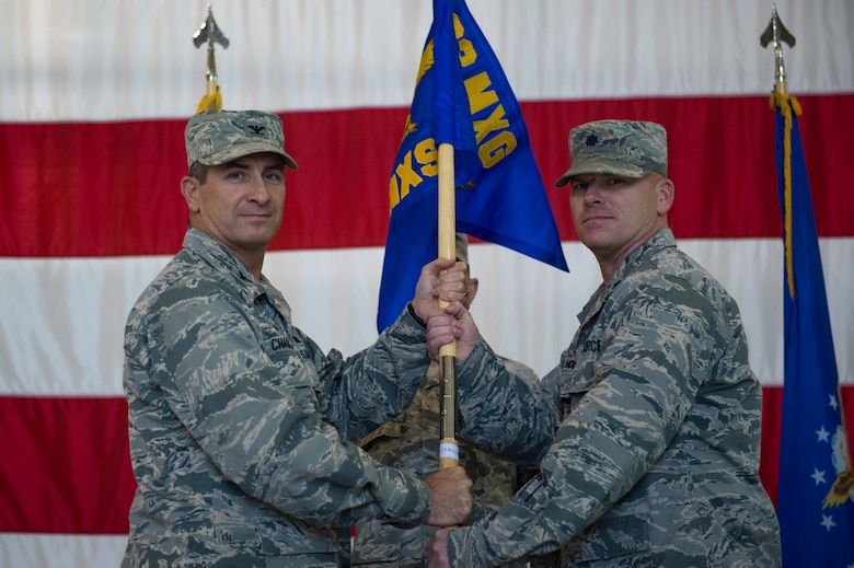 Col. John Chastain III, 23d Maintenance Group commander, left, presents Lt. Col. Neal Van Houten, 23d Maintenance Squadron commander, with the 23d MXS guidon during a re-designation ceremony, Nov. 9, 2017, at Moody Air Force Base, Ga. Van Houten took command of Air Combat Command's second largest squadron, leading the 800 men and women who are responsible for executing safe and reliable maintenance on aircraft systems, ground equipment and munitions to support the 23d Wing's attack and rescue missions. (U.S. Air Force photo by Senior Airman Greg Nash)