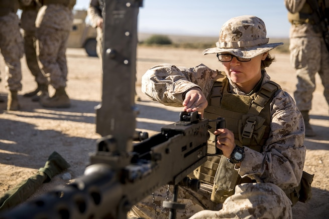 A marine sits on the ground operating a machine gun.