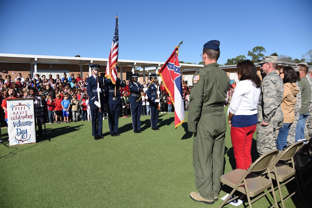 Col. C. Mike Smith, 81st Training Wing vice commander, and fellow audience members honor the flag during the Jeff Davis Elementary School Veterans Day celebration Nov. 10, 2017, in Biloxi, Mississippi. During the event, students recited the Pledge of Allegiance and sang several patriotic songs. Keesler Air Force Base leadership, honor guardsmen and base personnel attended the event. (U.S. Air Force photo by Kemberly Groue)