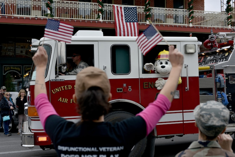 Parade participants wave flags as a Goodfellow Air Force Base fire truck drives by during the Veteran's Day parade in San Angelo, Texas, Nov. 11, 2017. The city hosted its annual parade in honor of those serving and those who have served the country.