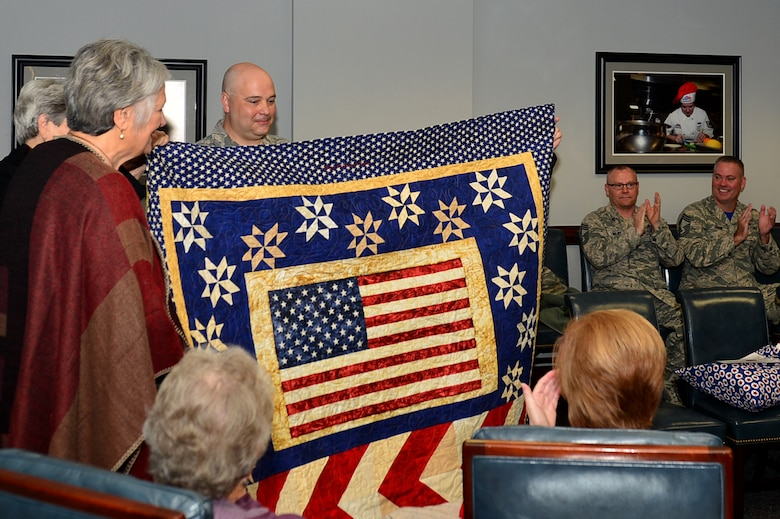U.S. Air Force Chief Master Sgt. Thomas Boslet, 20th Operations Group superintendent, displays the quilt for Capt. Salvador Cruz, 20th Fighter Wing F-16CM Fighting Falcon pilot, during a Quilts of Valor Foundation event at Shaw Air Force Base, South Carolina, Nov. 9, 2017.