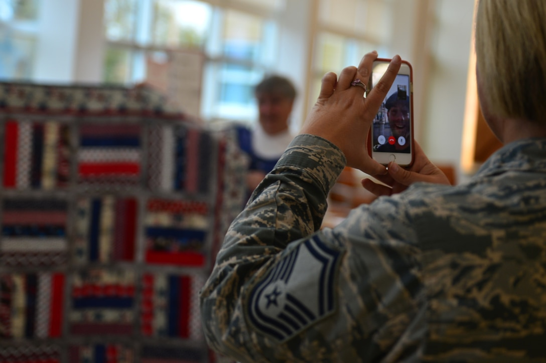 U.S. Air Force Senior Master Sgt. Heather Gulsby, 20th Medical Operations Squadron (MDOS) superintendent, video calls Airman 1st Class Daniel Caraglio, 20th MDOS mental health technician, to show him his quilt during a Quilt of Valor Foundation event at Shaw Air Force Base, South Carolina, Nov. 9, 2017.