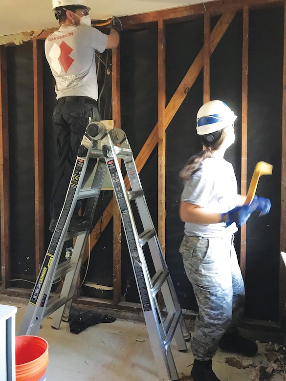 Tech. Sgt. Cody Smeltzer, 445th Aerospace Medicine Squadron, and Jennifer Bentley, a fellow Team Rubicon volunteer, gut a room that once contained more than two feet of water as a result of Hurricane Harvey.