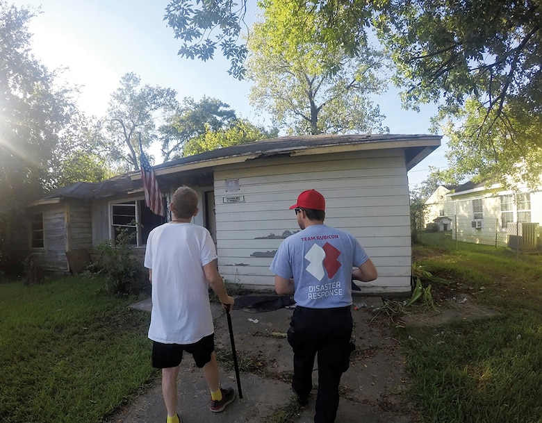 Tech. Sgt. Cody Smeltzer, 445th Aerospace Medicine Squadron, walks with Bruce, a disabled Vietnam veteran, to assess his home that was damaged during Hurricane Harvey