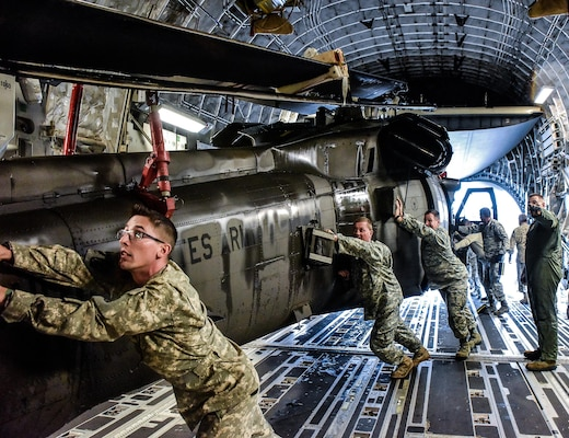 Tennessee National Guard Soldiers push a UH-60 Black Hawk into a C-17 aircraft carrier Sept. 13 at Joint Base Berry Field, Nashville, Tenn.