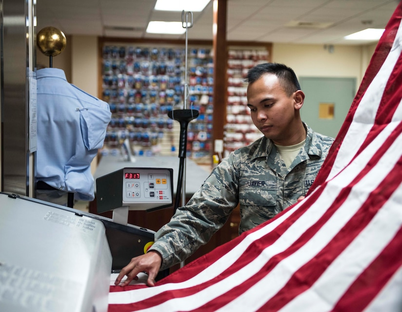 Air Force Senior Airman John Paul Javier presses the U.S. flag for use during mortuary affairs operations at Dover Air Force Base, Del., Oct. 24, 2017. Army photo by Master Sgt. Brian Hamilton