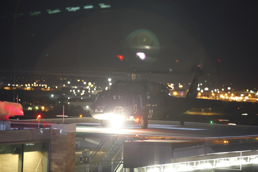 Helicopter lands at night on hospital's helipad.