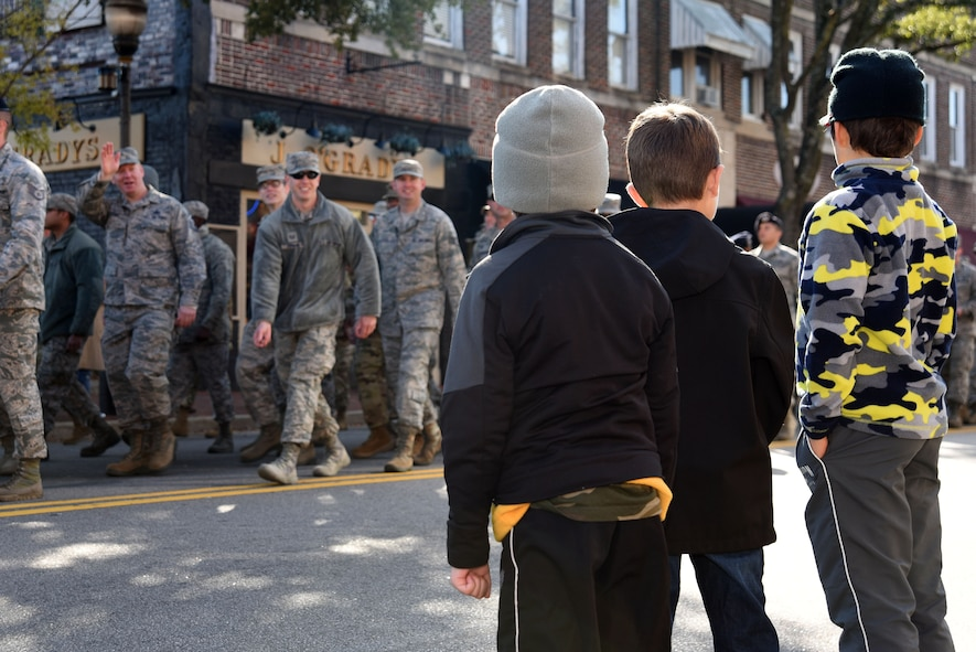 Children watch as U.S. Airmen and Soldiers walk past during a Veterans Day Celebration parade in Sumter, South Carolina, Nov. 11, 2017.