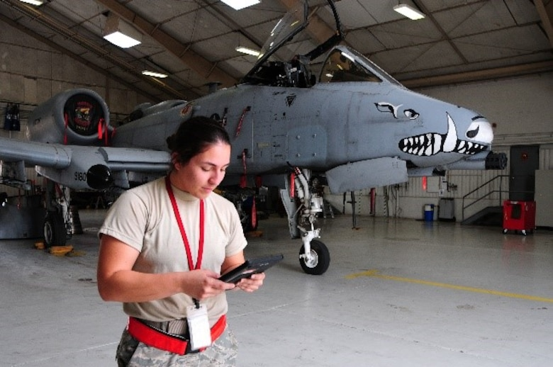 Senior Airman Amanda Gonzales, 924th Fighter Group crew chief, checks her technical orders before beginning maintenance on an A-10 Thunderbolt II in a hangar on Davis-Monthan Air Force Base.