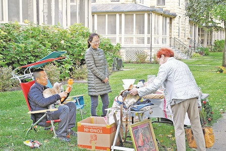 Lt. Col. Byung Min, U.S. Army Garrison Fort Riley, makes balloon swords for kids who come by while his wife Eunice entertains an interested customer during the post wide yard sale Oct. 7. The Mins said if traffic picks up and more kids come by, they would also bring out the cotton candy machine.