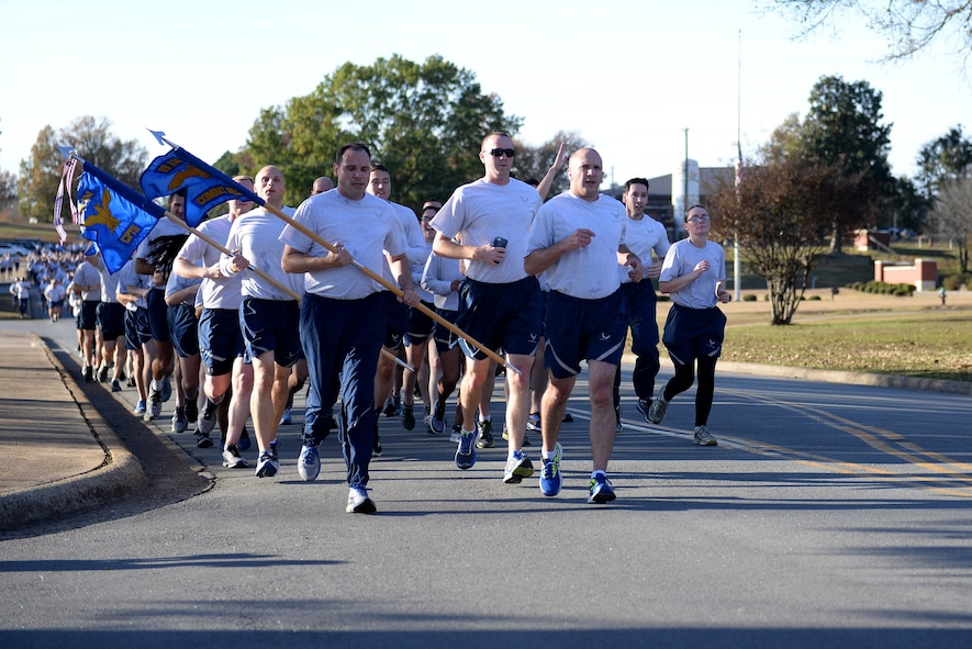 A group of people in Air Force physical training uniforms run in a formation to commemorate Veterans Day Nov. 9, 2017 at Little Rock Air Force Base, Ark.