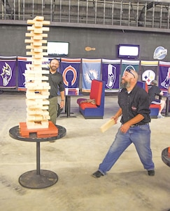 Richard Schott, processing staff member of the Defense Contract Management Agency, stands behind the GIANT Jenga as he watches co-worker Michael Furness, hiring and human resource staffer of the DCMA during the garrison Organizational Day Oct. 5 at Custer Hill Bowling Center.