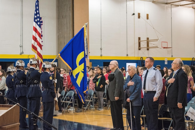 Retired Lt. Col. Clarence Wolgemuth, third from right, stands during the national anthem as the Caesar Rodney High School Air Force Junior Reserve Officer Training Corps Honor Guard presents the Colors Nov. 9, 2017, at Dover Air Force Base Middle School on Dover AFB, Del. During the Veterans Day celebration, students recognized Wolgemuth as this year's DAFBMS Veteran of Honor. (U.S. Air Force photo by Roland Balik)